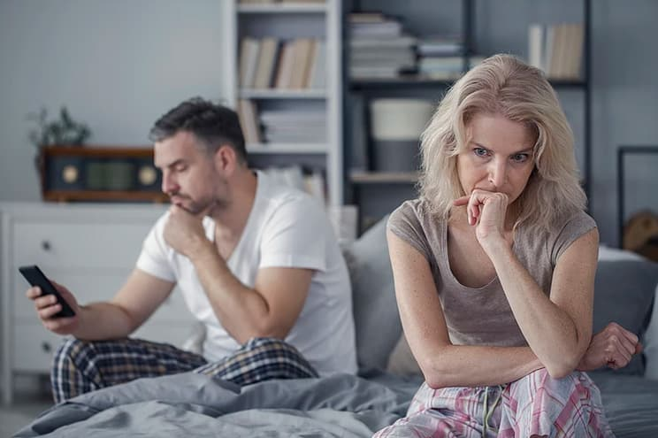 Woman in bed with her husband worried and very anxious.