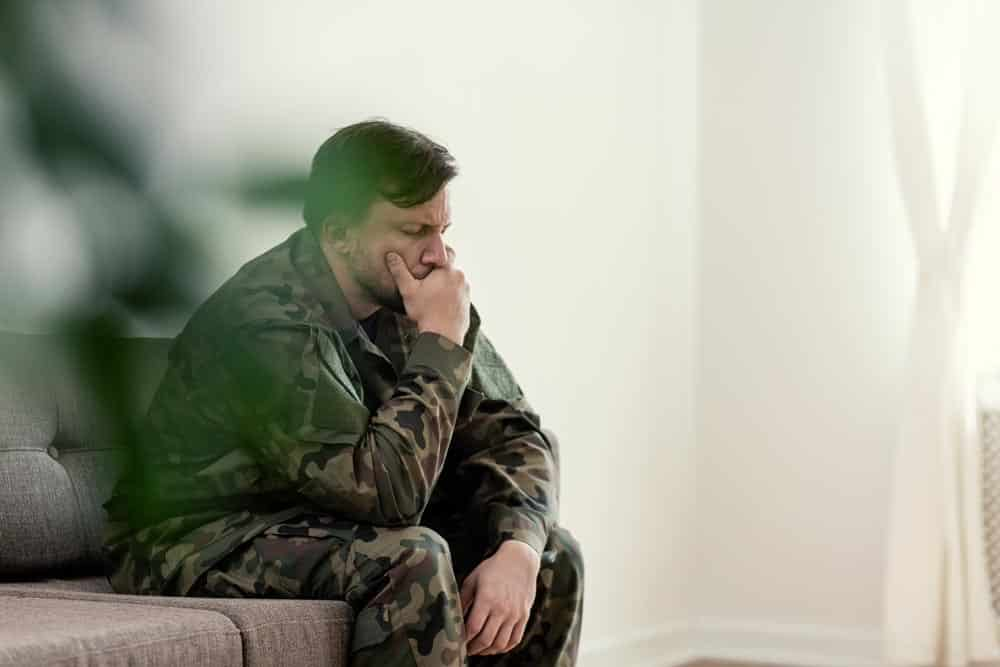 Sad soldier in uniform covering his mouth while sitting on a sof
